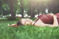 Bella ragazza che si trova sull'erba nel parco di estate Fotografia Stock