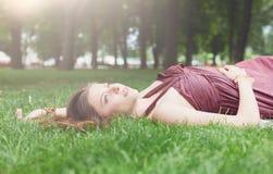 Bella ragazza che si trova sull'erba nel parco di estate Fotografia Stock Libera da Diritti