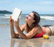 Bella ragazza che si trova sulla spiaggia che legge un libro con il riassunto fresco Fotografia Stock