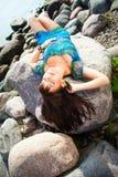 Bella ragazza che si trova sulle pietre della spiaggia immagine stock libera da diritti