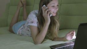Bella ragazza che si trova sullo strato che funziona al suo computer portatile Risponde alla chiamata su uno smartphone archivi video
