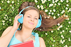Bella ragazza che si trova in un prato e che ascolta la musica Fotografie Stock