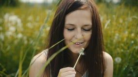 Bella ragazza che soffia un dente di leone e sorridere stock footage