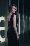 Bella ragazza che sta shopwindow vicino sulla via della città di notte Fotografia Stock