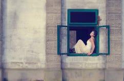 Bella ragazza che sta su una finestra aperta Fotografia Stock