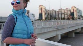 Bella ragazza che sta sul lungomare che tiene una bottiglia di acqua archivi video