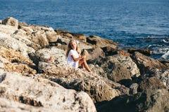 Bella ragazza che sta sulla spiaggia rocciosa Fotografia Stock Libera da Diritti