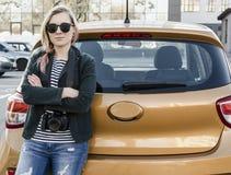 Bella ragazza che sta vicino alla sua automobile arancio luminosa Fotografie Stock Libere da Diritti