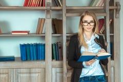 Bella ragazza che sta vicino alle scale con un libro Immagini Stock Libere da Diritti