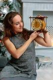 Bella ragazza che tiene gli orologi in mani nella stanza di natale immagini stock