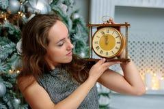 Bella ragazza che tiene gli orologi in mani nella stanza di natale fotografie stock