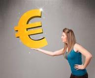 Bella ragazza che tiene un grande segno dell'euro dell'oro 3d Immagini Stock Libere da Diritti