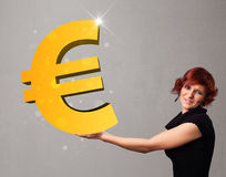 Bella ragazza che tiene un grande segno dell'euro dell'oro 3d Immagine Stock