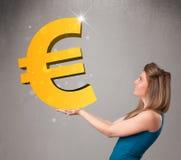 Bella ragazza che tiene un grande segno dell'euro dell'oro 3d Fotografie Stock