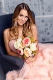 Bella ragazza che tiene un mazzo dei fiori e che si siede sulla sedia nell'interno immagine stock