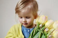 Bella ragazza che tiene un mazzo dei tulipani gialli Immagine Stock