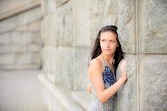 Bella ragazza circa la parete di pietra Fotografia Stock