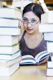Bella ragazza circondata dai libri delle biblioteche Fotografia Stock Libera da Diritti