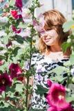 Bella ragazza circondata dalla malva variopinta dei fiori fotografia stock