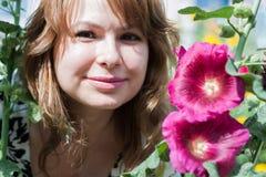 Bella ragazza circondata dalla malva variopinta dei fiori fotografie stock libere da diritti