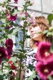 Bella ragazza circondata dalla malva variopinta dei fiori Fotografia Stock Libera da Diritti