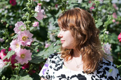 Bella ragazza circondata dalla malva variopinta dei fiori immagine stock libera da diritti
