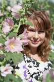 Bella ragazza circondata dalla malva variopinta dei fiori Immagine Stock