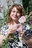 Bella ragazza circondata dalla malva variopinta dei fiori immagini stock libere da diritti