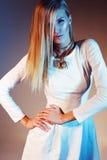 Bella ragazza in collana bianca dell'oro e del vestito con capelli diritti biondi lunghi Immagini Stock