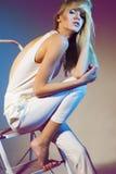 Bella ragazza in collana bianca dell'oro e del vestito con capelli diritti biondi lunghi Fotografia Stock