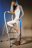Bella ragazza in collana bianca dell'oro e del vestito con capelli diritti biondi lunghi Immagine Stock