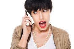 Bella ragazza sorpresa mentre per mezzo del telefono cellulare Fotografie Stock
