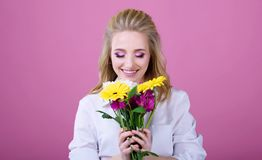 Bella ragazza con bei fiori su un fondo rosa fotografie stock libere da diritti