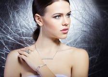 Bella ragazza con bei gioielli costosi alla moda, collana, orecchini, braccialetto, anello, filmante nello studio Immagini Stock