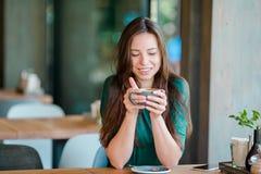 Bella ragazza con caffè caldo che mangia prima colazione al caffè all'aperto Caffè bevente della giovane donna urbana felice Immagine Stock