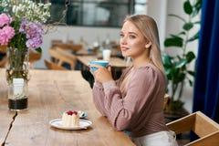Bella ragazza con capelli biondi e gli occhi azzurri che beve caffè in caffè fotografia stock
