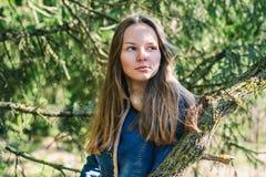 Bella ragazza con capelli biondi lunghi in un rivestimento blu del denim in una foresta verde un giorno di molla soleggiato immagine stock