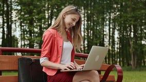 Bella ragazza con capelli biondi su un banco di parco che lavora al suo computer portatile Ragazza che per mezzo del computer por video d archivio