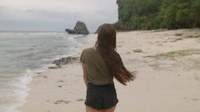 Bella ragazza con capelli lunghi che cammina lungo la riva della spiaggia in Bali video d archivio