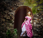 Bella ragazza con capelli lunghi intrecciati in una treccia, in corsetto e vestito rosa magnifico immagine stock