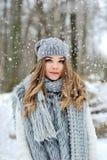 Bella ragazza con capelli ricci lunghi in sciarpa tricottata nella foresta di inverno sotto i fiocchi di neve Fotografia Stock
