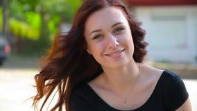 Bella ragazza con capelli rossi che sorride, ridente e facente un fronte e guardante in camera video d archivio