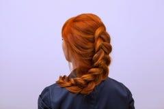 Bella ragazza con capelli rossi lunghi, intrecciati con una treccia francese, in un salone di bellezza fotografia stock