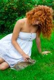 Bella ragazza con capelli rossi sulla natura con un coniglio in sue mani Immagine Stock