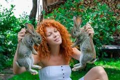 Bella ragazza con capelli rossi sulla natura con un coniglio in sue mani Immagine Stock Libera da Diritti