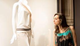 Bella ragazza con capelli scuri che stanno davanti ad un negozio di lusso e che guardano una nuova collezione Fotografia Stock Libera da Diritti