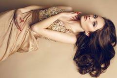 Bella ragazza con capelli scuri lussuosi in vestito dallo zecchino che posa allo studio Fotografia Stock