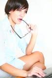 Bella ragazza con funzionamento di vetro sul computer portatile Fotografie Stock Libere da Diritti