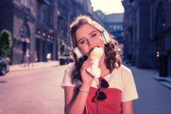 Bella ragazza con gli occhi azzurri che gode del gusto del gelato delizioso fotografia stock libera da diritti