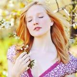 Bella ragazza con gli occhi chiusi in albero di fioritura che gode della natura fotografie stock